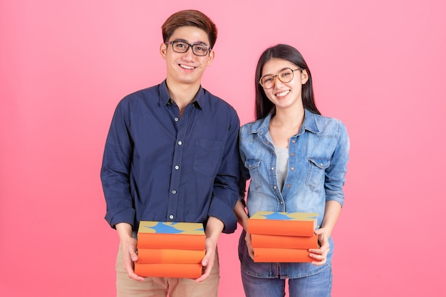 Portrait friendly teenage man and woman wearing eyeglasses and holding books