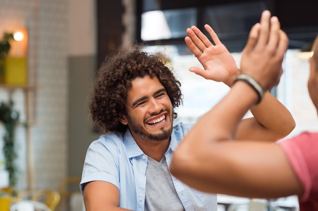 Portrait of friends giving high five at cafe while having lunch