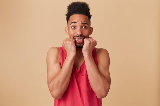 Ritratto di uomo spaventato, afroamericano con barba e acconciatura afro. indossare canottiera rossa. inorridito, spaventato dal muro beige pastello