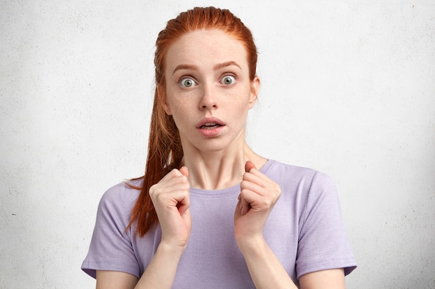 Portrait of frightened ginger female model has amazed look stares at camera with unexpected expression, has bated breath
