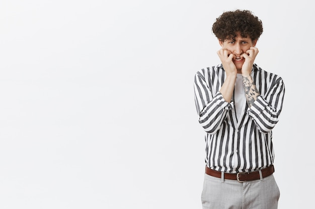 Portrait of frightened male coward with curly hair tattoos and moustache biting fingernails looking from under forehead scared and nervous panicking being terrified standing in striped shirt and pants