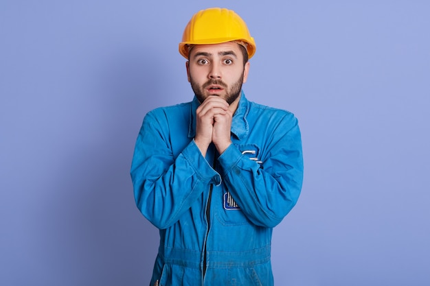 Portrait of frightened shocked young builder opening eyes widely, , putting hands together, being afraid . working problems concept.