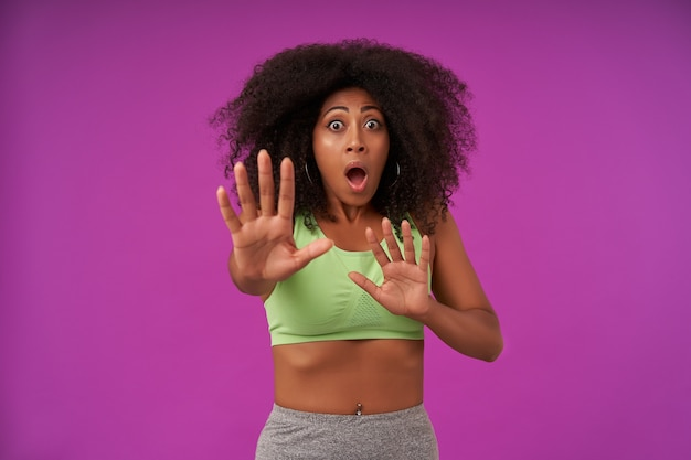 Portrait of frightened young dark skinned woman with curly hair wearing sporty clothes isolated on purple with raised hands in stop gesture