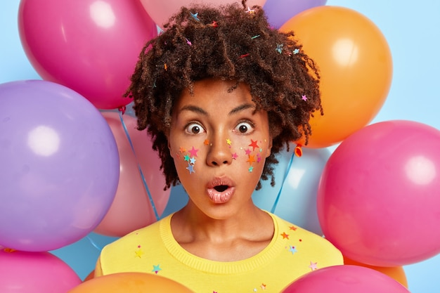 Portrait of frightened young woman posing surrounded by birthday colorful balloons