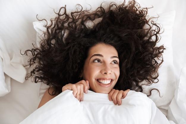 Портрет сверху веселой женщины 20-х годов с темными кудрявыми волосами, смотрящей вверх, лежащей в постели на белом белье с счастливой улыбкой