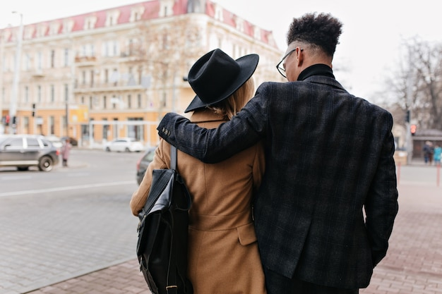 Ritratto dal retro dell'uomo africano in vestito elegante che cammina per la città con la sua ragazza. ragazzo riccio nero che abbraccia donna affascinante in cappello e cappotto beige.