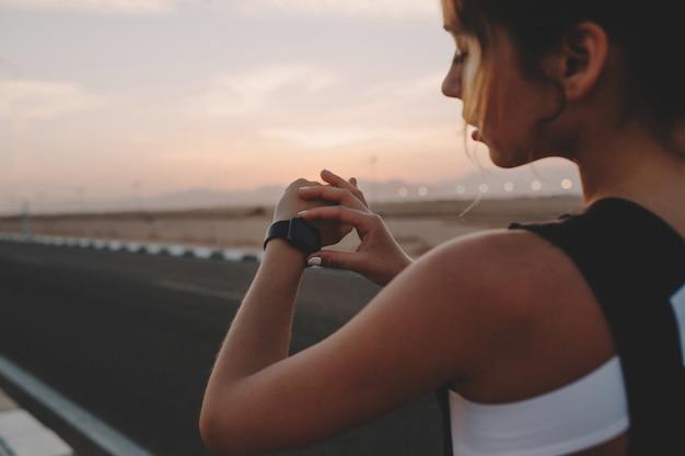 道路上の手で時計を見てスポーツウェアの後ろから美しい若い女性の肖像画。晴れた夏の早朝、ファッショナブルなスポーツウーマンのトレーニング、モチベーション