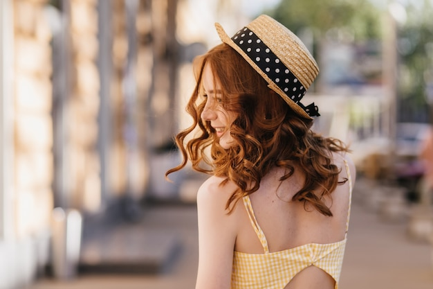 Portrait from back of carefree ginger woman in hat. outdoor photo of pretty adorable lady in summer yellow outfit.