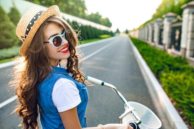 Ritratto dal retro della ragazza carina con lunghi capelli ricci in cappello alla guida di una bici su strada. indossa farsetto, occhiali da sole blu. sta sorridendo alla telecamera.