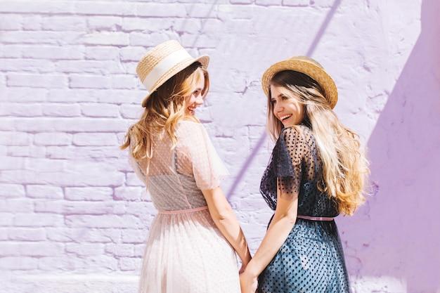 Ritratto dal retro di ragazze eleganti in cappelli estivi di paglia scherzando e ridendo