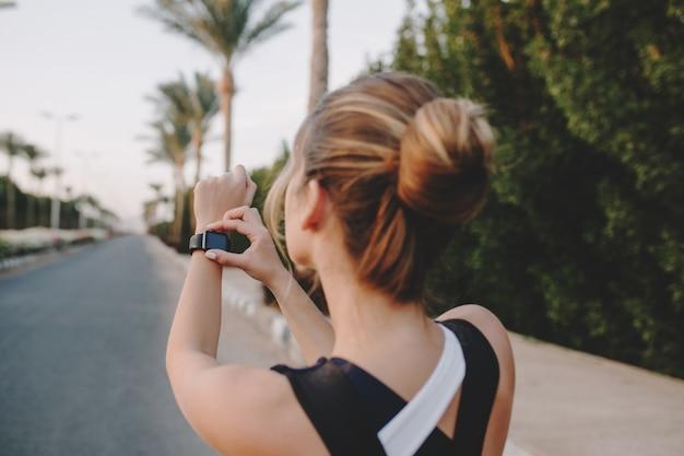 熱帯都市のヤシの木が付いている通りの手でモダンな時計を見て後ろのファッショナブルなスポーツウーマンからの肖像画。魅力的な女性のトレーニング、トレーニング、健康的なライフスタイル、勤勉