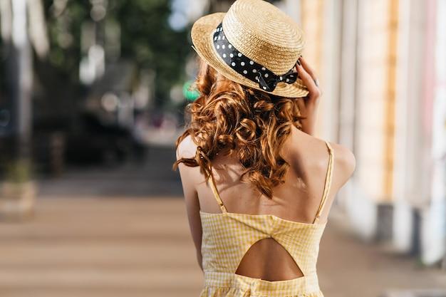 Ritratto dal retro della ragazza dello zenzero in cappello di paglia decorato con nastro. colpo esterno di elegante signora dai capelli rossi in abito giallo in posa sulla strada.