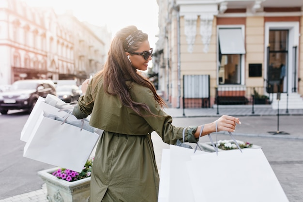 Portrait from back of gorgeous brunette woman in dark sunglasses hurrying home after shopping in weekend