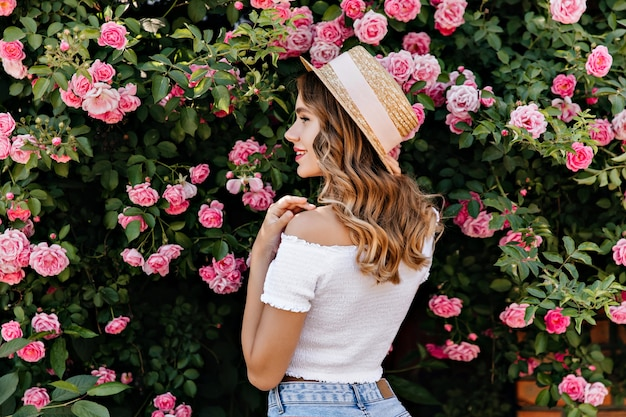 Portrait from back of gorgeous caucasian girl looking at pink roses. outdoor photo of fashionable female model in hat standing near blossoming bush.