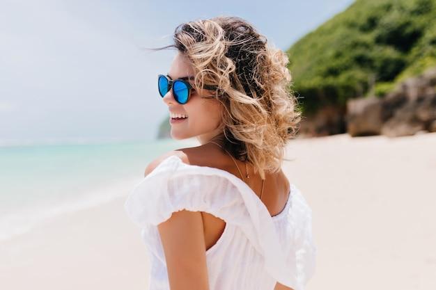 Ritratto dal retro della donna abbronzata interessata agghiacciante al resort. colpo all'aperto di donna adorabile con capelli chiari ondulati che camminano intorno alla spiaggia.