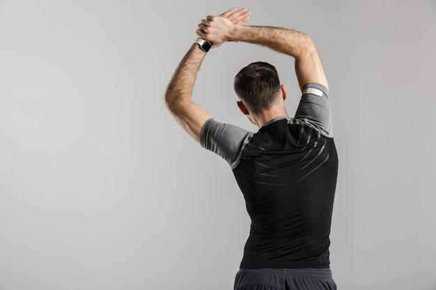 회색 벽에 격리된 채 운동을 하는 운동복 차림의 운동선수 뒤에서 찍은 초상화