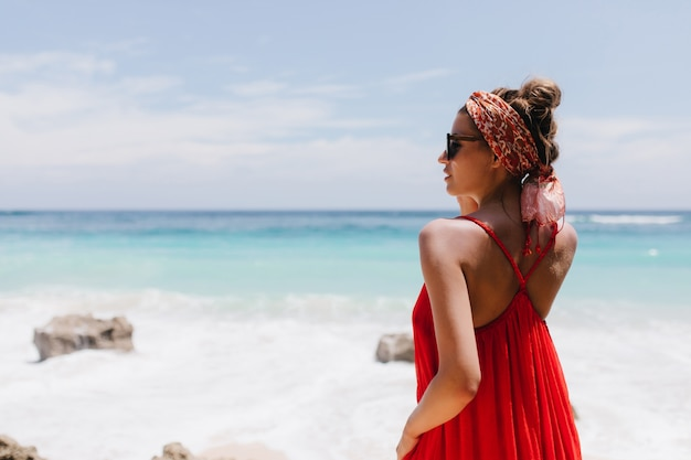 地平線を見ている日焼けした肌を持つのんきな女の子の後ろからの肖像画。海の海岸で冷やして眺めを楽しんでいる赤い服装で幸せな白人女性モデルの写真。