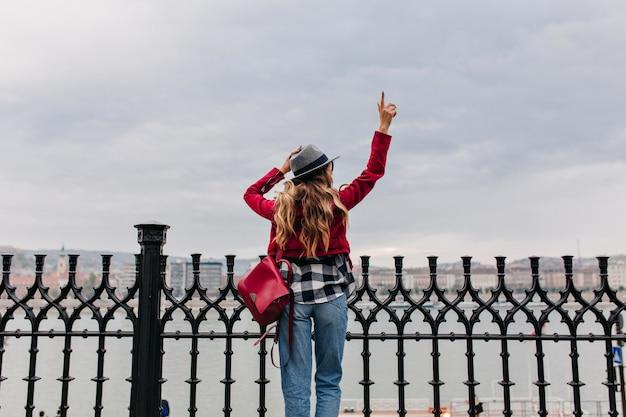 寒い朝に街を見て赤いバックパックとのんきな女性の後ろからの肖像画