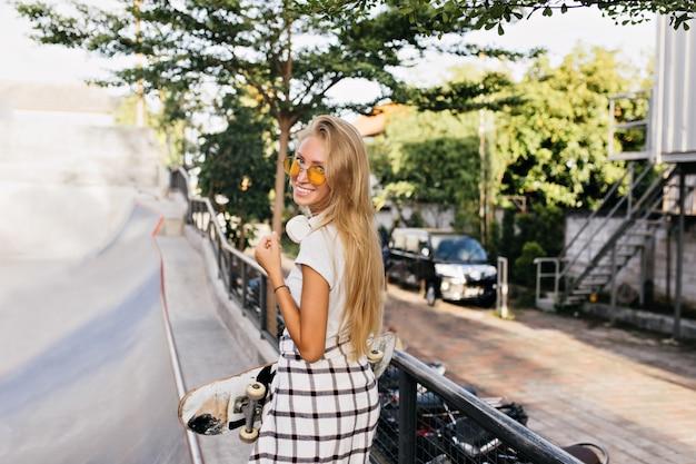 스케이트 보드를 들고 웃 고 있으면 백인 여자 뒤에서 초상화.