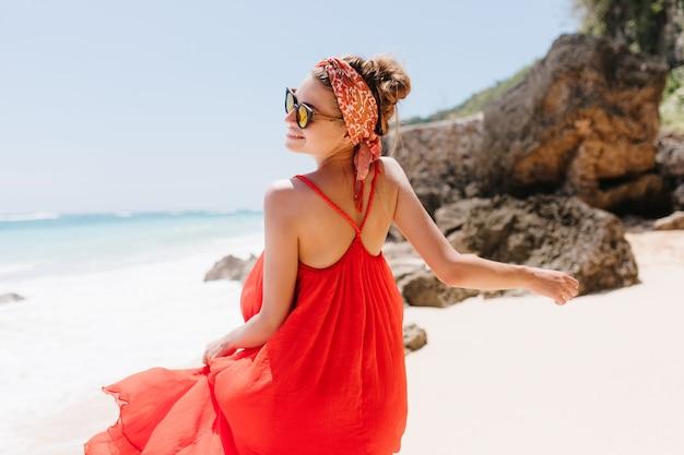 夏の暖かい日に人生を楽しんでいる嬉しい白人の女の子の後ろからの肖像画。ビーチで踊る赤いドレスを着たヨーロッパの魅惑的な女性の屋外写真