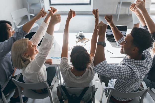 Портрет со спины радостных студентов, сидящих вместе за столом и поднимающих руки. фотография в помещении команды внештатных специалистов, развлекающихся после тяжелой работы в офисе.