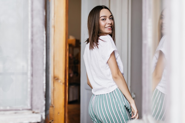 家で楽しんでいる白いtシャツの笑顔の女性の後ろからの肖像画。朝にリラックスしてうれしい茶色の髪の少女。