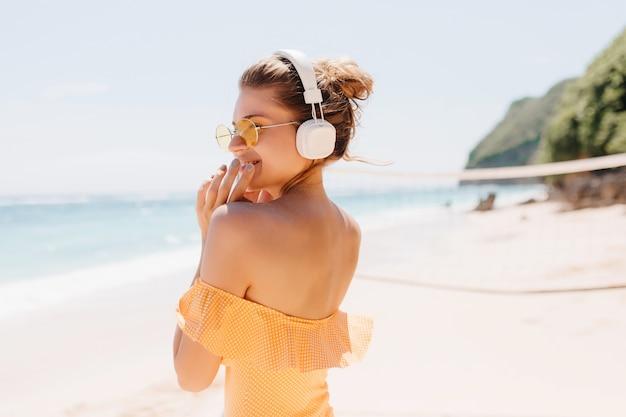 海の海岸で笑顔でポーズをとる壮大な女性の後ろからの肖像画。オレンジ色の水着と白いヘッドフォンで素敵な女の子を笑っている屋外の写真。