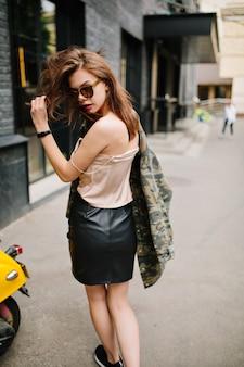ピンクのタンクトップと革のスカートのスタイリッシュな女の子の後ろからの肖像画は、真剣な表情で肩越しに見えます