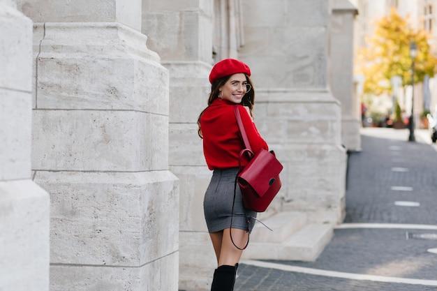 Портрет со спины стильной стройной девушки в очках, держащей кожаный рюкзак