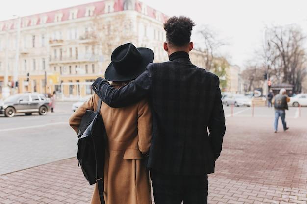 Портрет со спины высокого парня в темном костюме с вьющимися волосами, проводящими таймер с девушкой в бежевом пальто. наружное фото романтической пары, наслаждающейся видом на город.