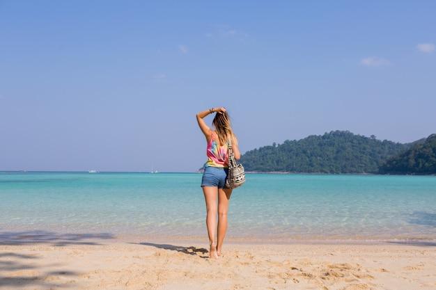 Портрет со спины загорелой молодой женщины, смотрящей на удивительный вид на синее море и горы
