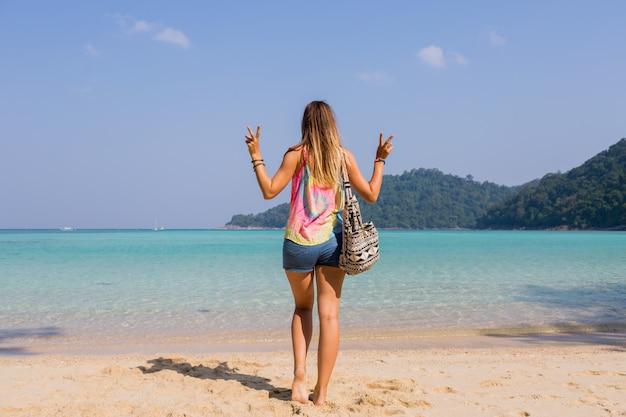 素晴らしい青い海と山の景色を探している日焼けした若い女性の後ろからの肖像画