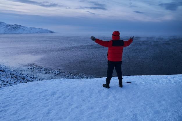 슬로우 모션으로 겨울 거친 물을 멀리보고 멀리 찾고 바다 앞에 서있는 defocus에 따뜻하게 옷을 입고 여자의 뒤에서 초상화