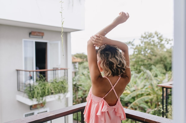 Portrait from back of positive young lady posing with hands up in hotel. graceful tanned girl stretching at balcony and enjoying city views.