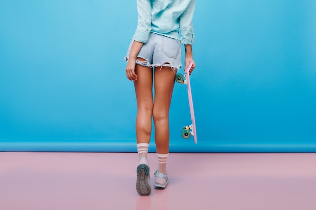 Portrait from back of sporty tanned woman wears cute socks and cotton shirt. indoor photo of graceful girl with bronze skin in denim shorts holding longboard.