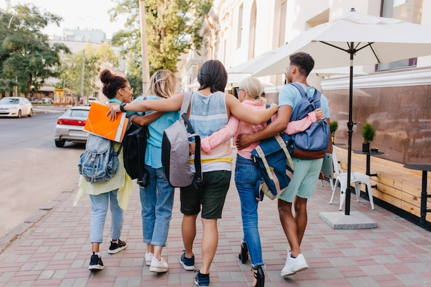 Portrait from back of students with stylish backpacks walking down the street after lectures in university. tall brunette young man embracing girls while spending time with them outdoot..
