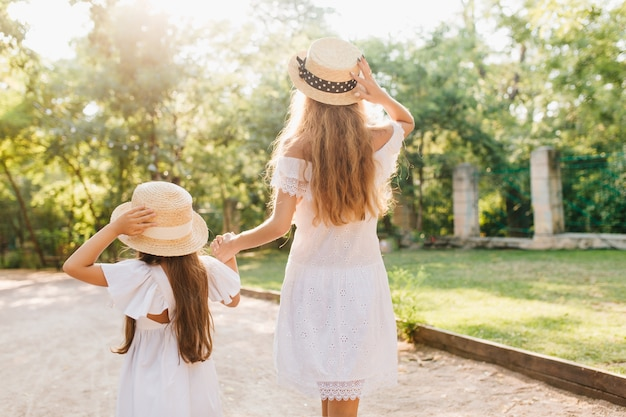 Portrait from back of tall tanned woman leading daughter down the street. blonde slim lady holding hands with little brunette girl, walking by lawn and fence in park.