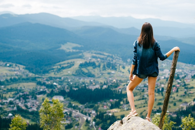 Portrait from behind of brunette girl sith wooden stick atnding on stone in the mountains with landscape view on background.