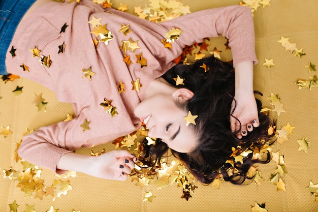 Portrait from above cheerful pretty young woman with curly brunette hair laying on beige couch in golden tinsels. smiling with closed eyes, enjoying rest at comfortable home