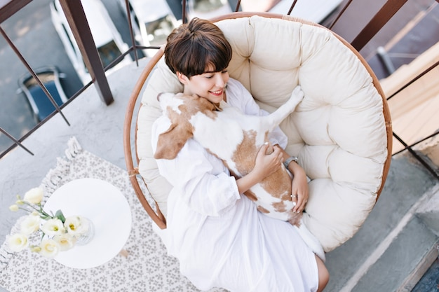 Portrait from above of cheerful young lady resting on balcony after shower and gently stroking pet. adorable girl spending time on terrace with beagle enjoying weekend