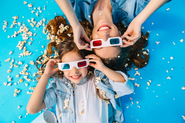 Portrait from above cute mother and daughter laying head to head isolated on blue floor. wearing 3d glasses, long brunette hair, having fun in popcorn, best weekends, free time with family
