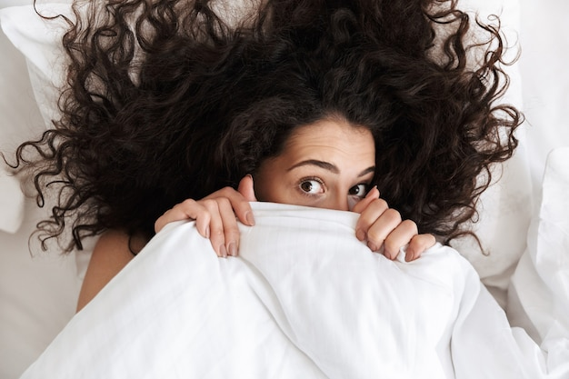 Portrait from above of cute woman 20s with dark curly hair covering her face with white blanket, while lying in bed after waking up in morning