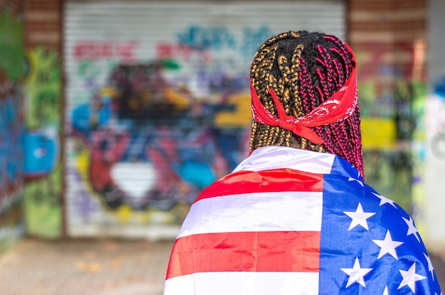 Portrait from behind of an exotic black woman with colored braids. covered with the united states flag. graffiti wall background.