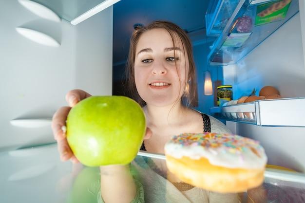 Portrait from inside the fridge of woman taking green apple