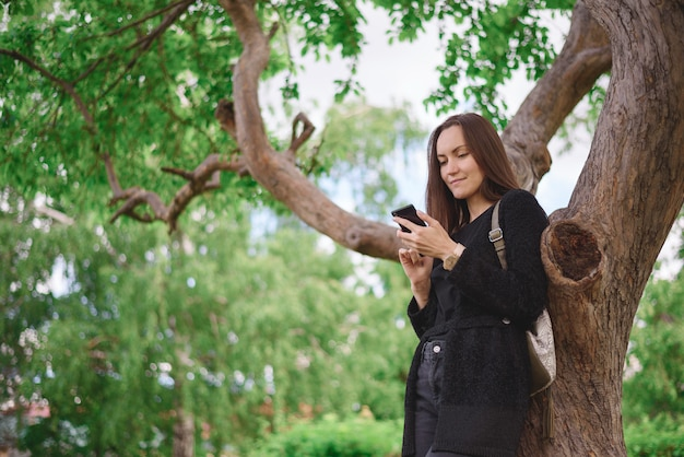 Portrait from the lower angle of a young woman in a black jacket with a smartphone in her hands on the background of a large branched tree. virtual communication, generation z