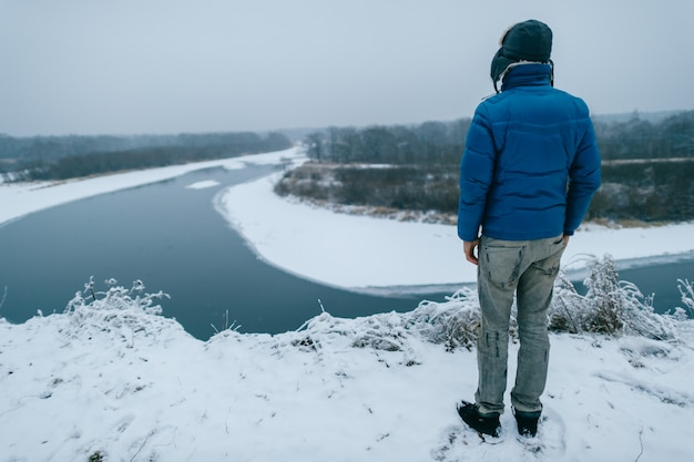 Portrait from behind of a man in winter clothes standing on the edge of a hill and looking at winter snowy river.