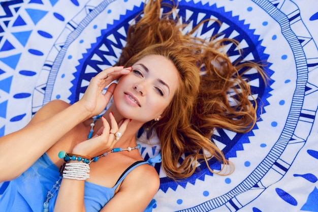 Portrait from above of smiling woman relaxing on beach towel in sunny summer day. stylish boho bracelets and necklace.