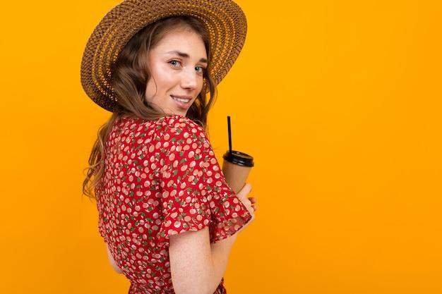 分離された黄色の彼女の手でコーヒーのグラスを持つ若い女の子の後ろからの肖像画