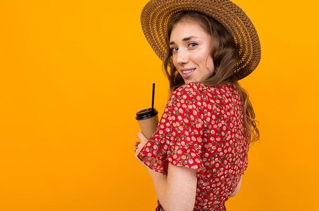 分離された黄色、彼女の手でコーヒーのグラスを持つ若い女の子の後ろからの肖像画