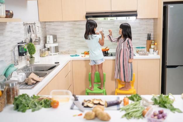 Портрет со спины двух маленьких детей, готовящих на кухне и получающих удовольствие